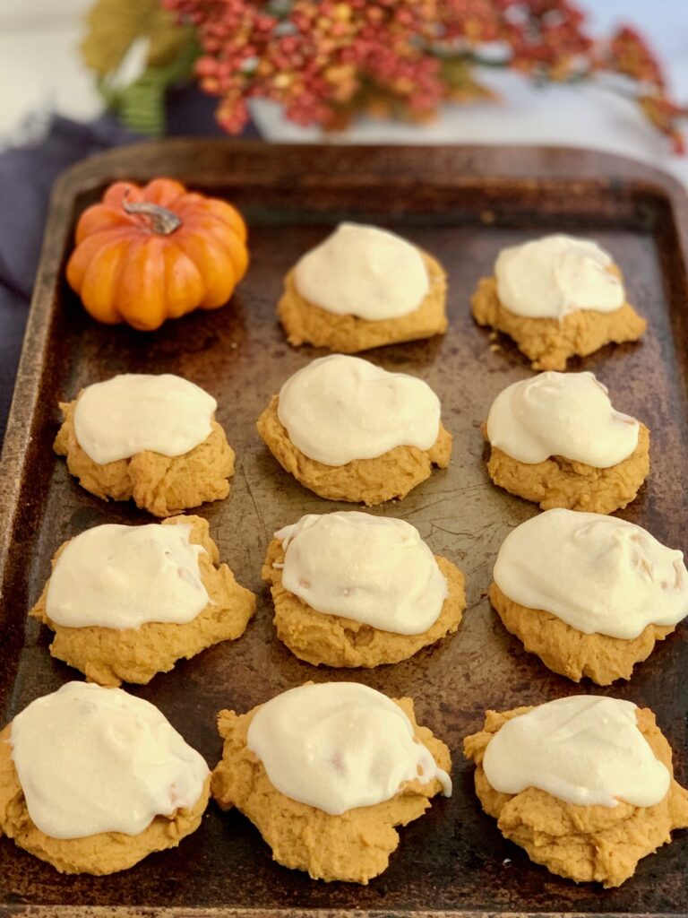 A sheet pan of pumpkin cookies with cream cheese frosting.