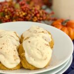 Pumpkin cookies with cream cheese frosting on a plate with a glass of milk