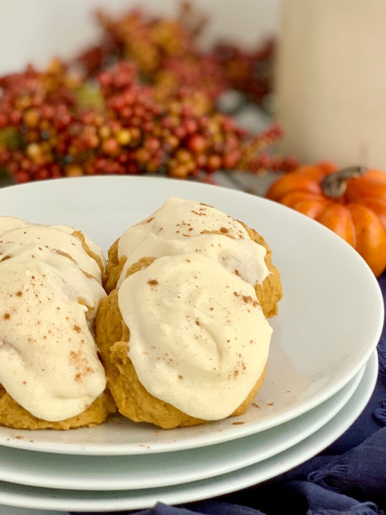 A plate full of pumpkin cookies with cream cheese frosting.