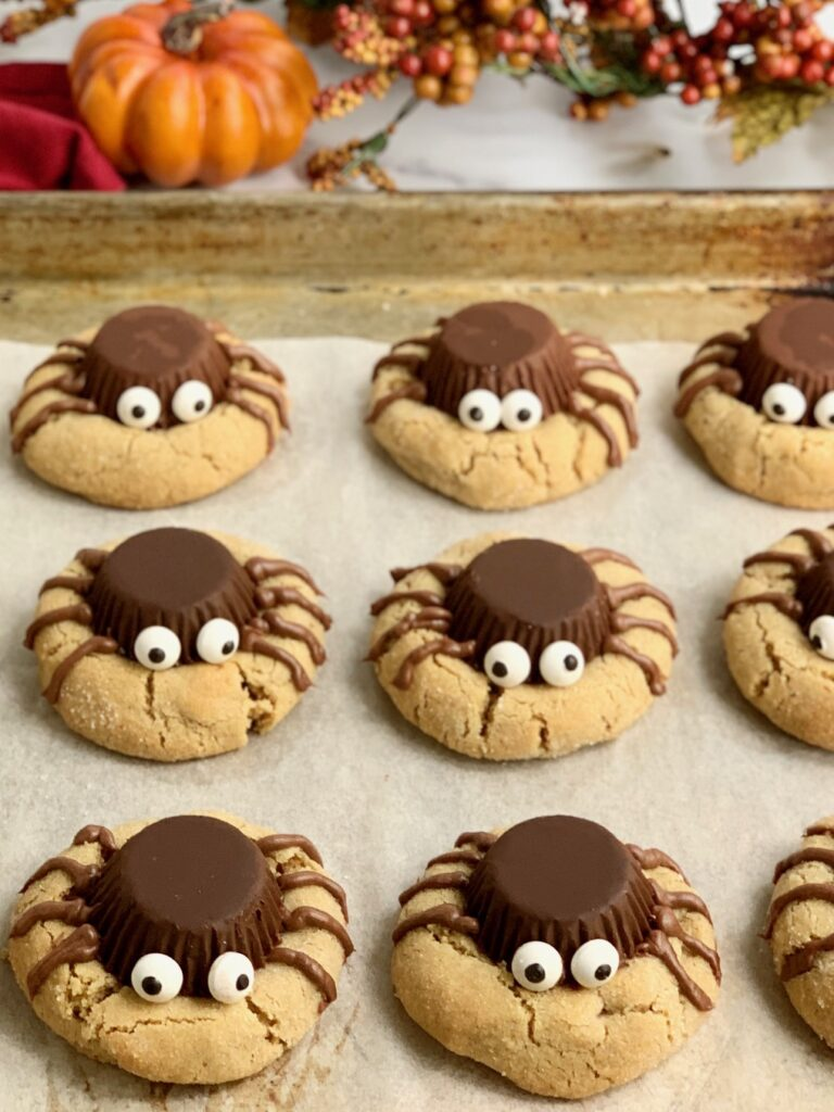 a baking sheet with peanut butter cookies topped with an upside down peanut butter cup, four frosting legs on each side and 2 googly eyes to look like a spider on  cookie