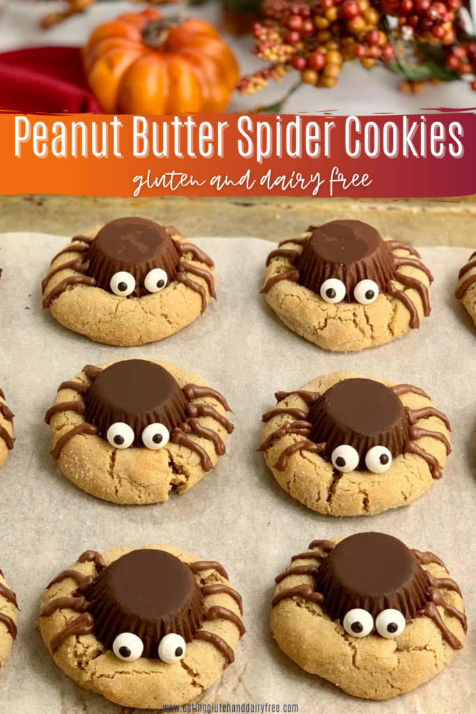 A baking sheet of peanut butter cookies with an upside down peanut butter cup. On the peanut butter cup is edible eyes with 4 icing spider legs on each side.