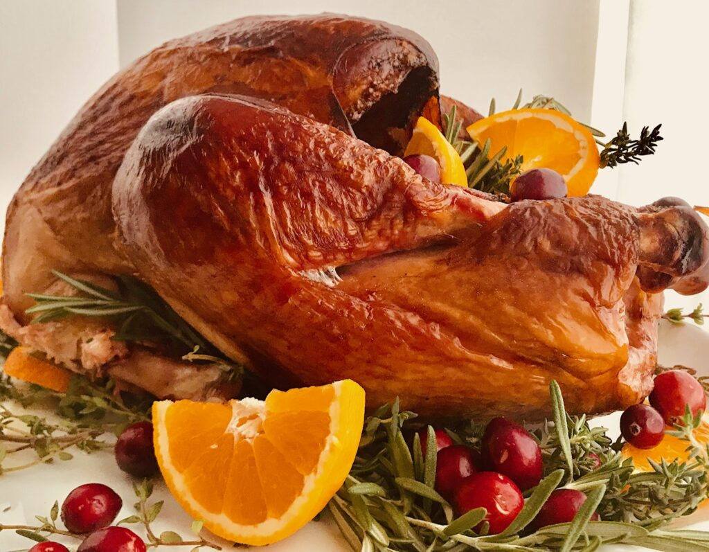 A smoked turkey on a serving platter with fresh sliced oranges, cranberries, and herbs.