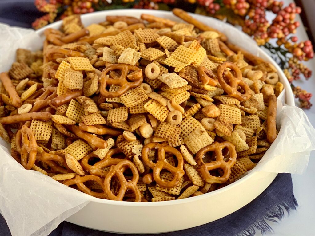 a large party bowl of chex party mix that has pretzels, peanuts, chex mix, and corn mix.