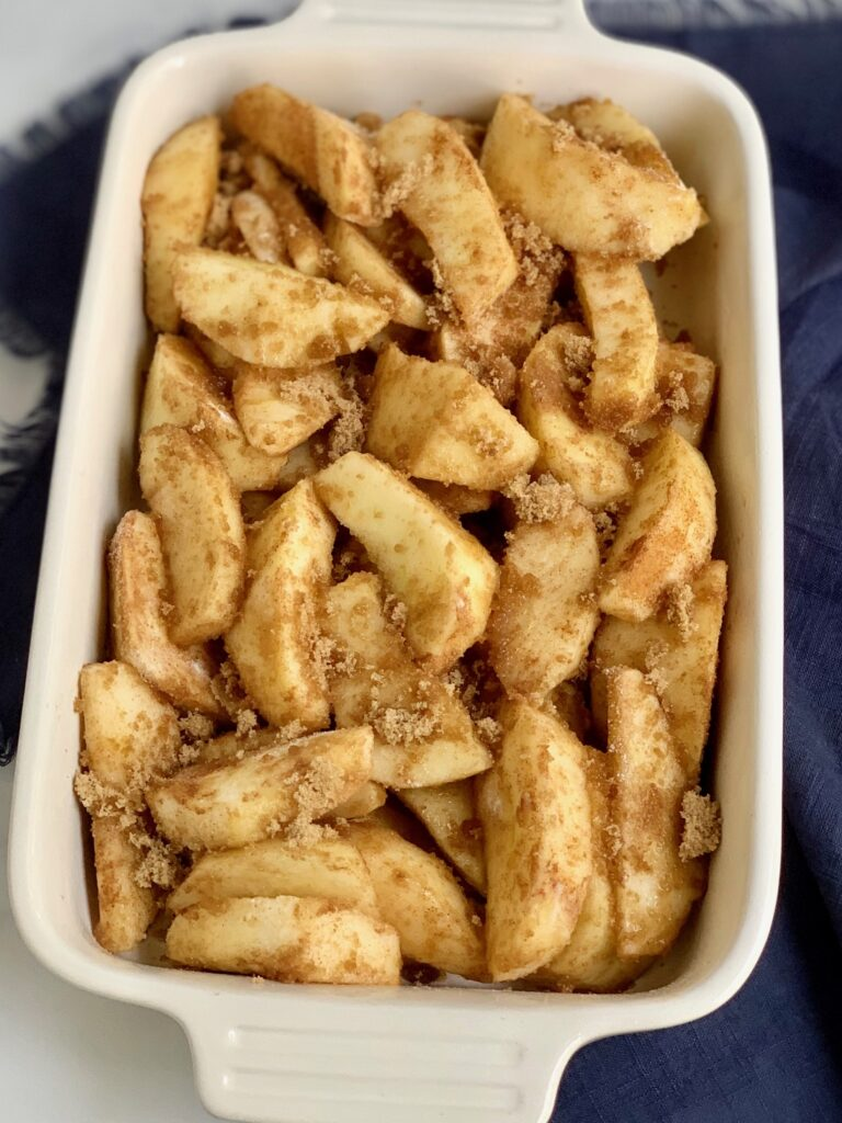 Sliced apples in a baking pan with with cinnamon, lemon juice, and brown sugar on them.