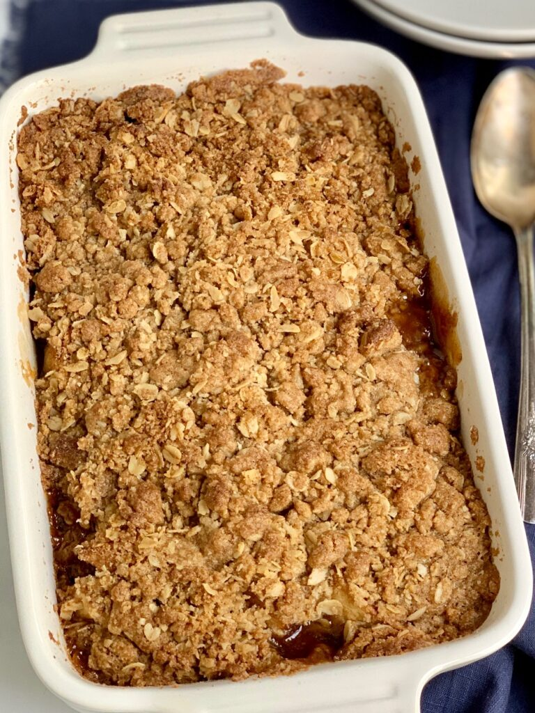 A baked pan of apples topped with a brown sugar, oatmeal, and butter topping.