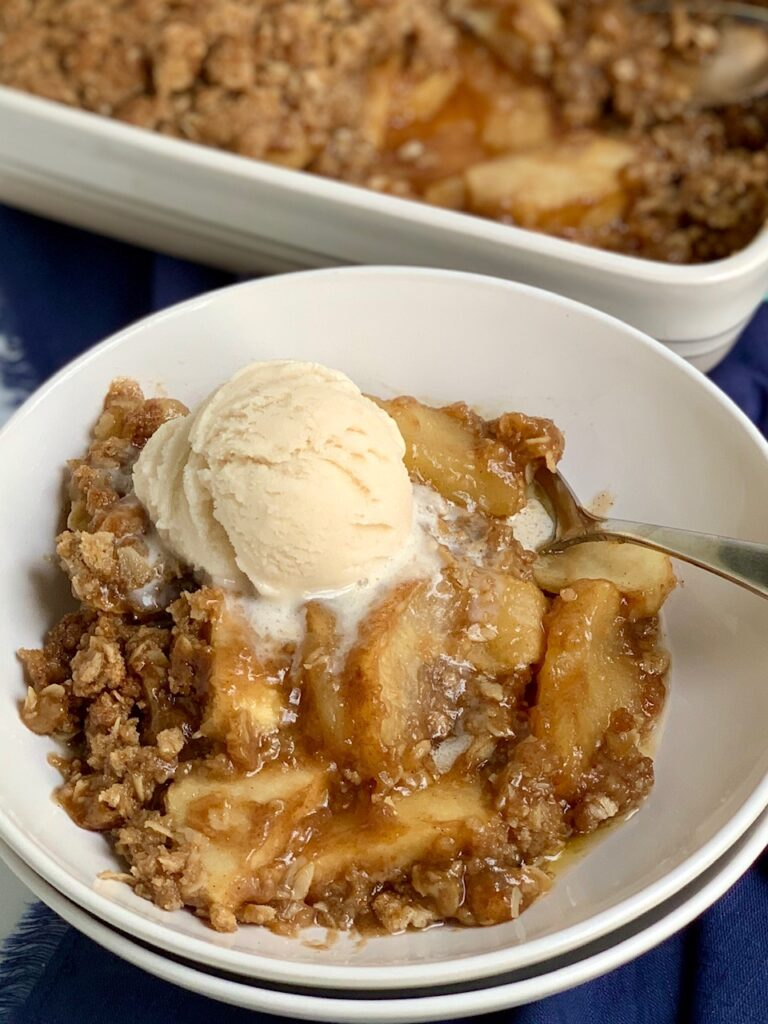 A bowl of sliced apples topped with a ooey gooey brown sugar, butter, and oatmeal mixture then with dairy free ice cream on top.