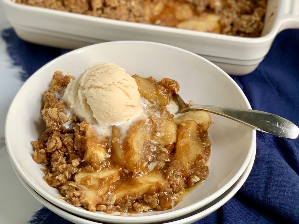 A big scoop of apple crisp with tender apple slices and gooey topping plus a dollop of dairy free ice cream