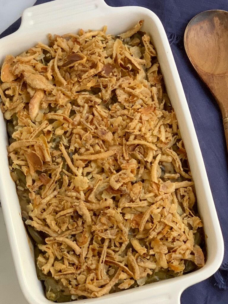 A baking dish with creamy mushroom soup. green beans, and crispy French fried onions on top.