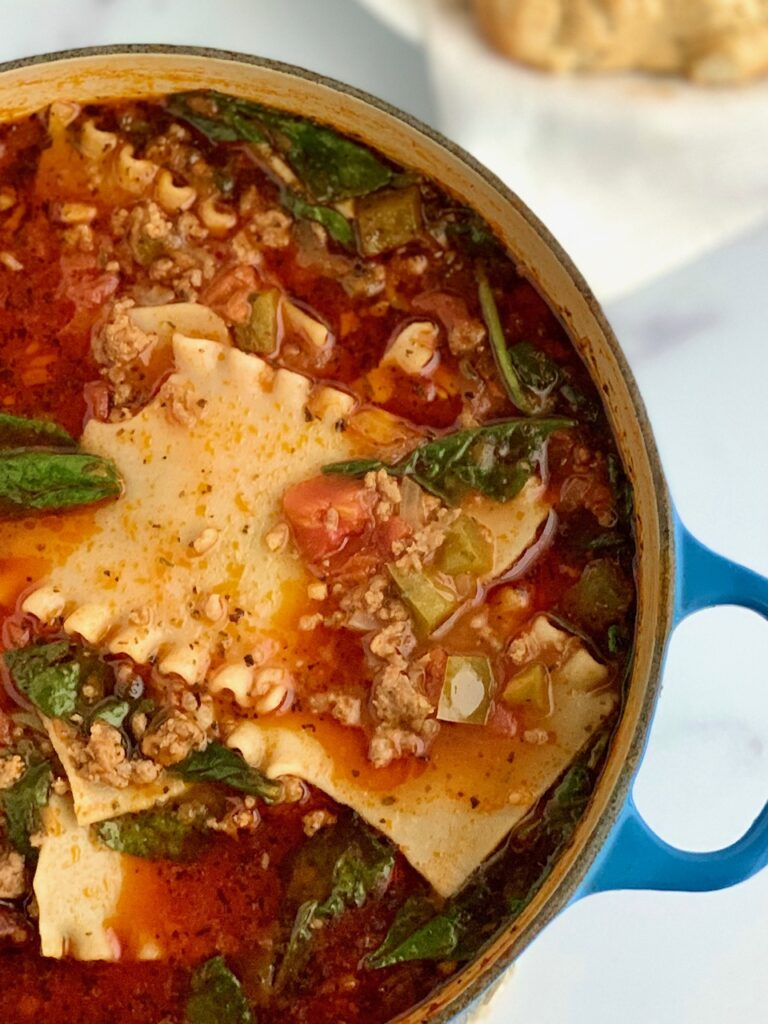 A serving bowl of lasagna soup with a dollop of dairy free ricotta and fresh basil.
