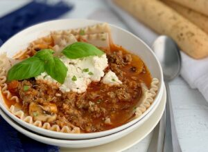 Lasagna soup with big tender lasagna noodles, chunks of ground beef, Italian sausage, and topped with dairy free ricotta next to 2 serving spoons.