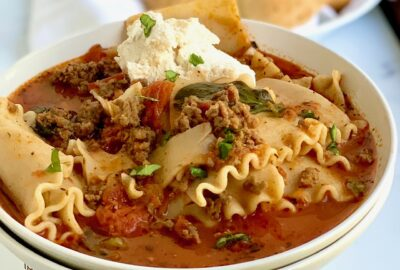 Serving bowl with lasagna soup and dinner rolls.