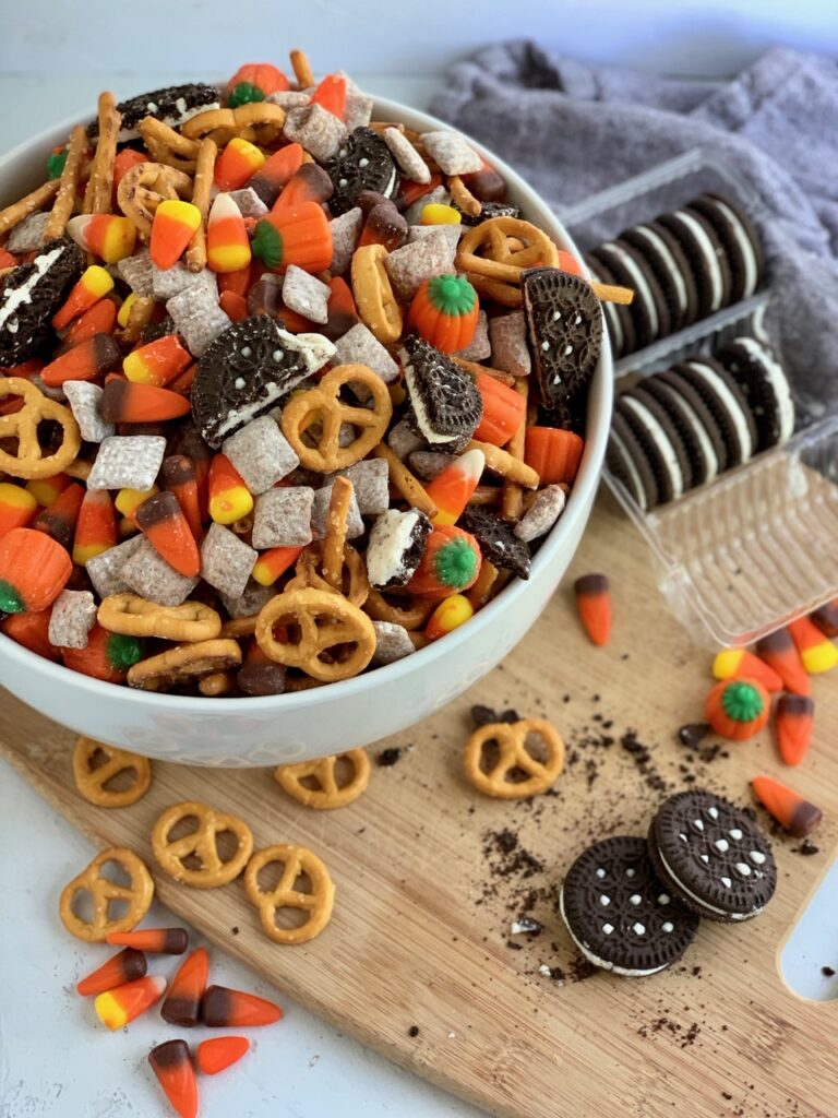 a bit party bowl of pretzels, puppy chow, candy corns, and oreo like sandwich cookies