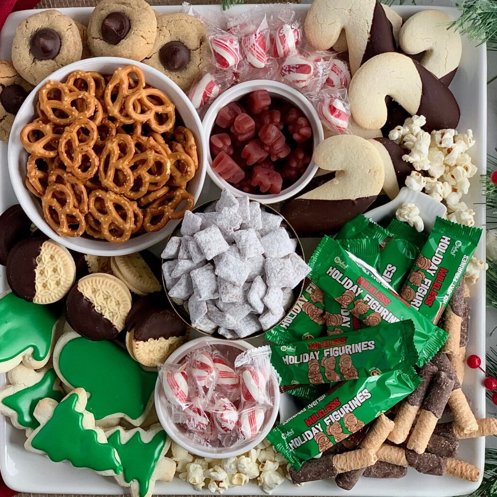 A large serving platter filled with pretzels, puppy chow, popcorn, sugar cookies, peppermint candies, cinnamon gummy bears, and chocolate dipped oreos.