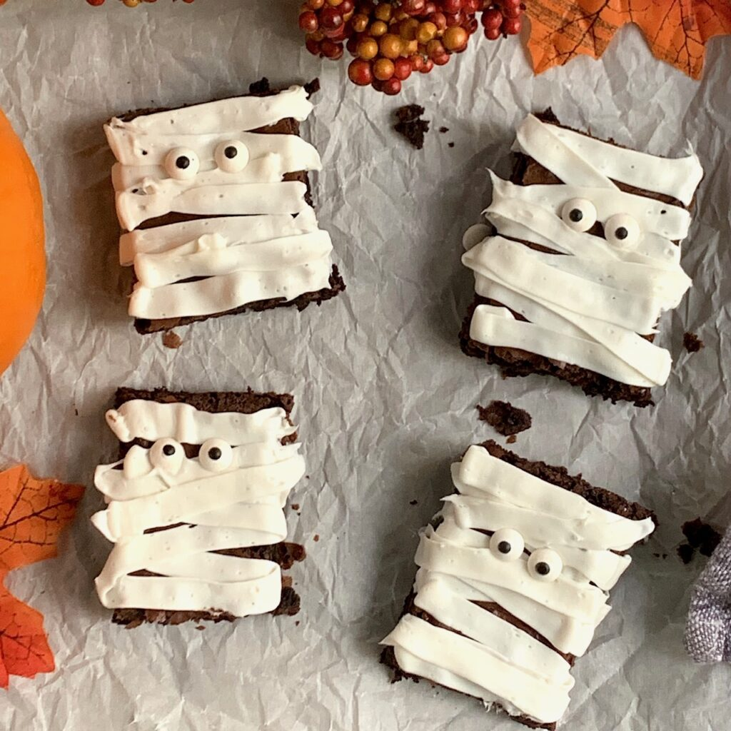 4 rectangular brownie's with white frosting draped across and google eyes to look like mummies