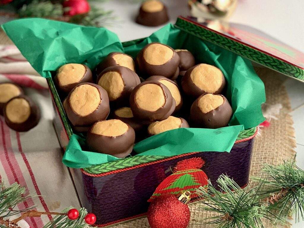 A Christmas tin filled  peanut butter balls dipped in melted chocolate.