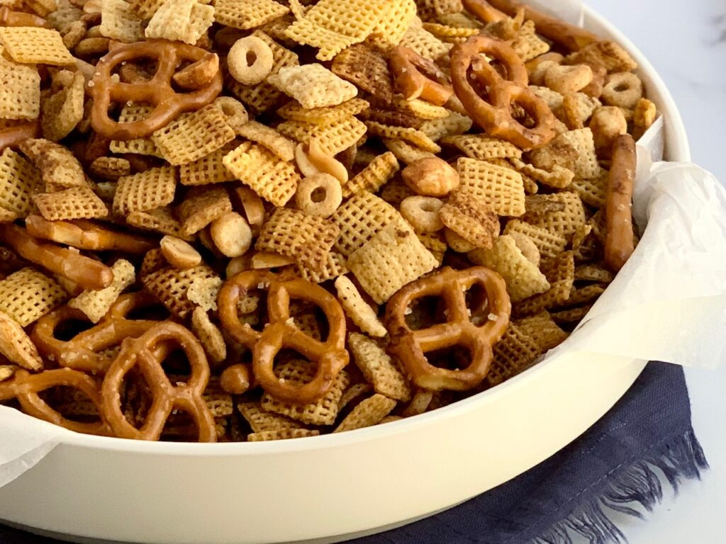 A serving platter full of pretzels, peanuts, rice chex cereal, corn chex cereal, and Whole O's.