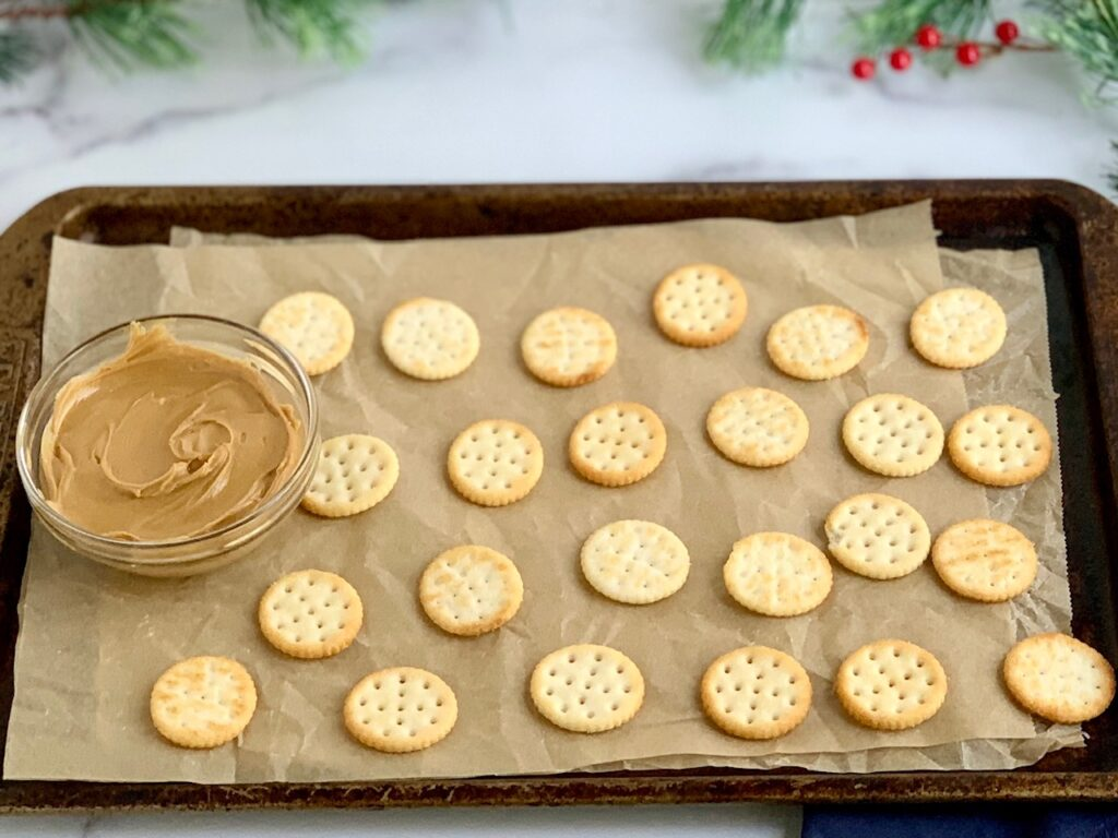 A baking sheet lined with wax paper and crackers on it.