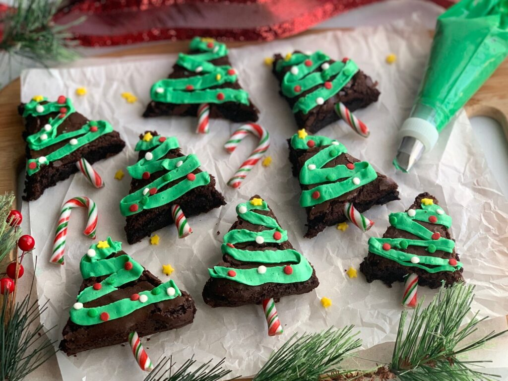 Brownies cut into a tree shape with zig zag green frosting topped with festive sprinkles.