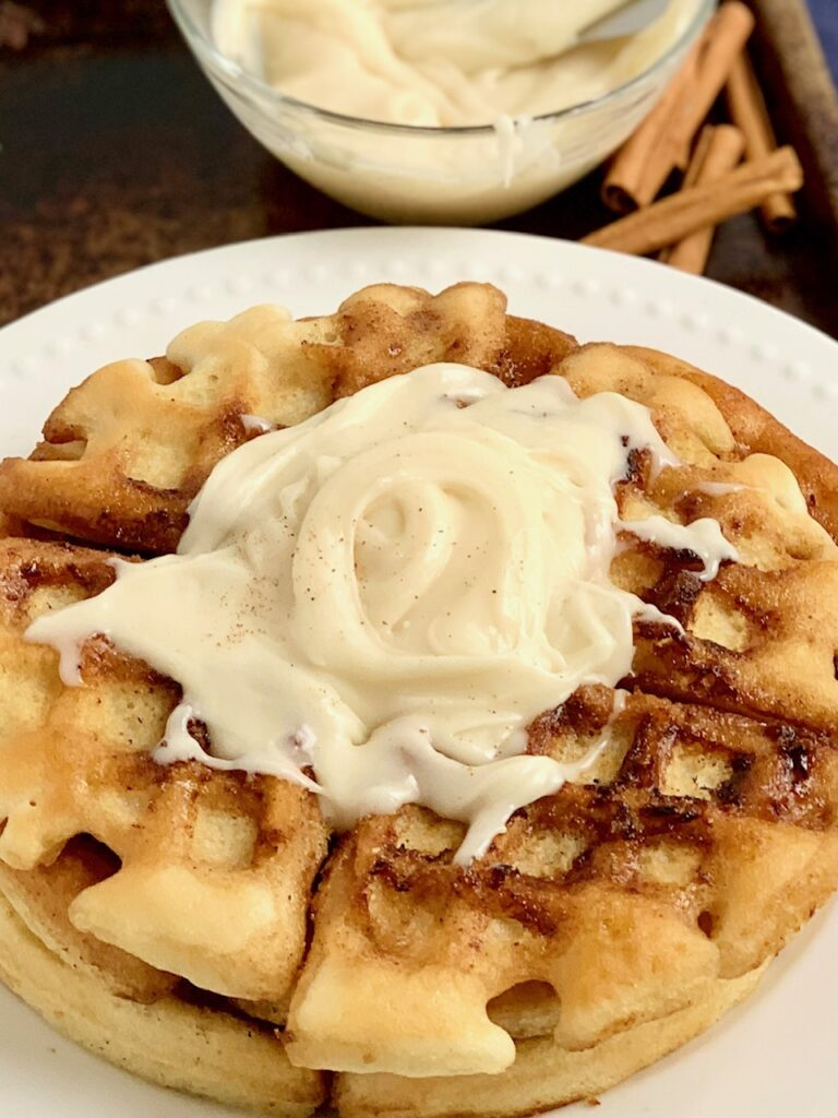 A white plate with 2 large waffles on it. The waffles have a cinnamon swirl mixture in the them and topped with a creamy frosting.