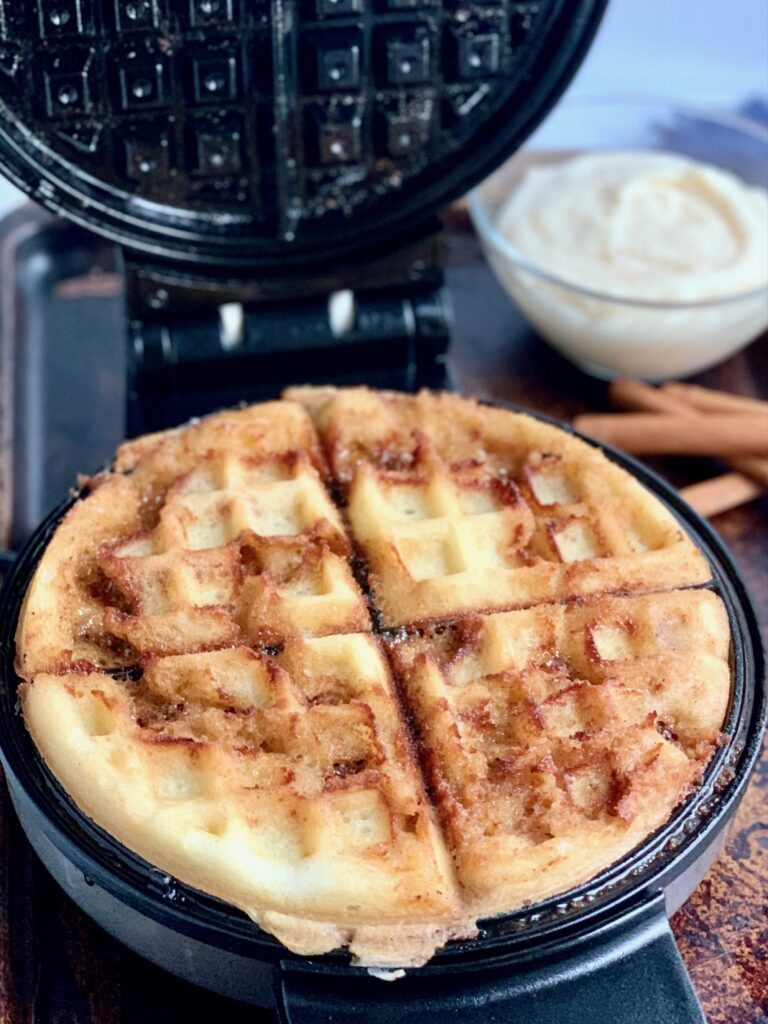A waffle in a waffle maker after it has been made with a caramelized cinnamons sugar mixture on it.