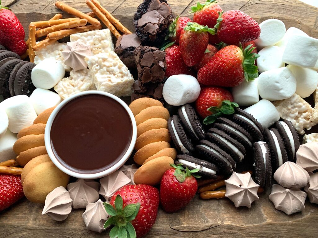 A large serving platter with oreo like cookies, vanilla wafers, strawberries, marshmallows, brownie bites, and meringue kisses.