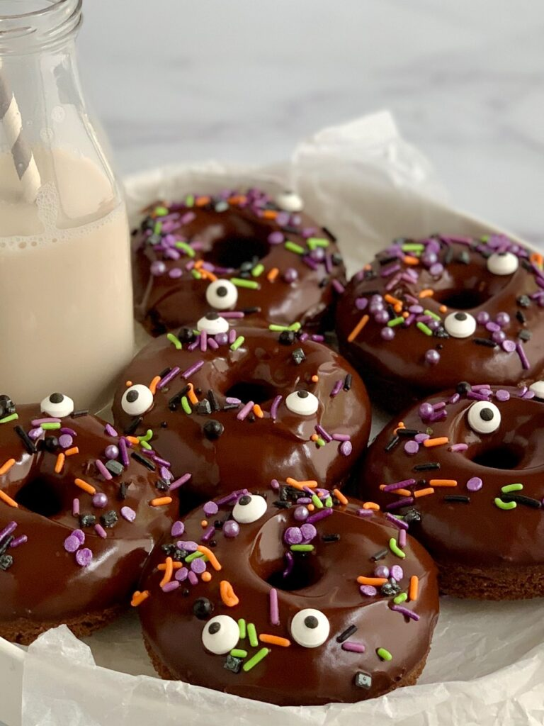 A serving plate filled with 6 double chocolate donuts topped with chocolate ganache and Halloween themed sprinkles.