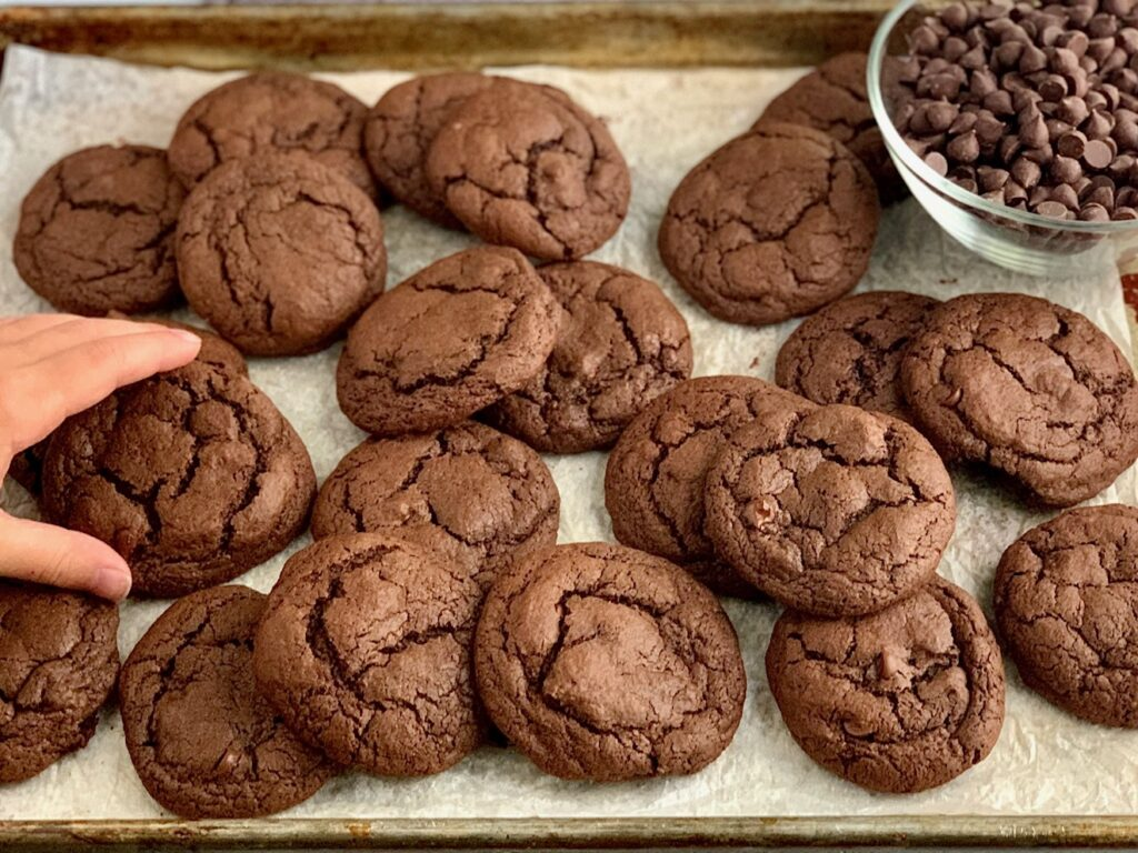 A hand reaching for a fudgy brownie cookies