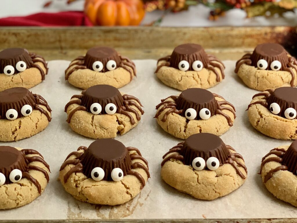Peanut butter cookies with upside down peanut butter cups to look like spiders with edible eyes and frosting for legs.