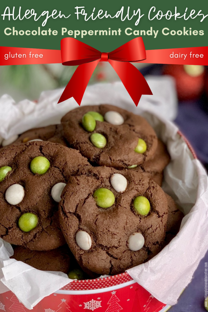 A festive red holiday tin filled with chocolate cookies featuring green and white candies on the top.
