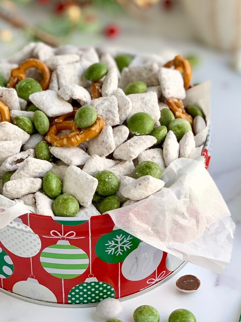 A colorful tin of puppy chow, pretzels, and white and green peppermint candies.