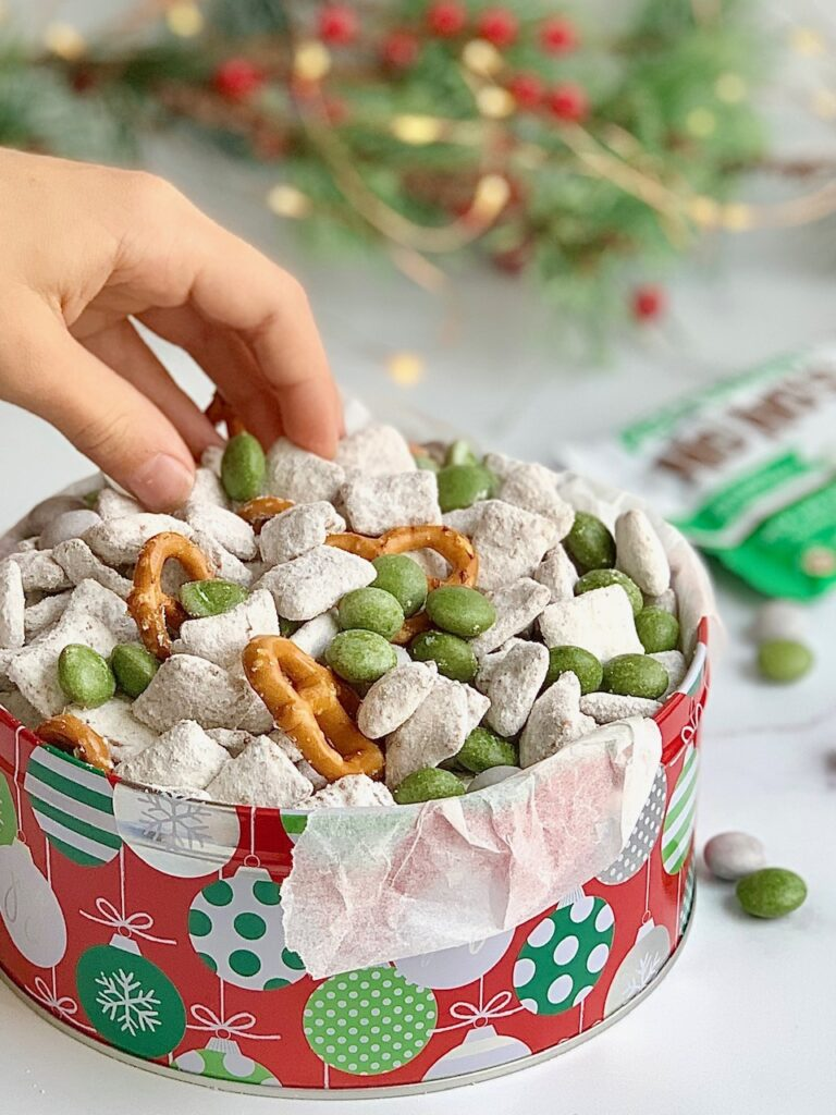 A holiday tin filled with homemade puppy chow, pretzels twists, and No Whey Peppermint No No's and a hand reaching in to grab some.