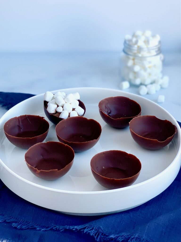 A platter full of 6 empty chocolate wells.