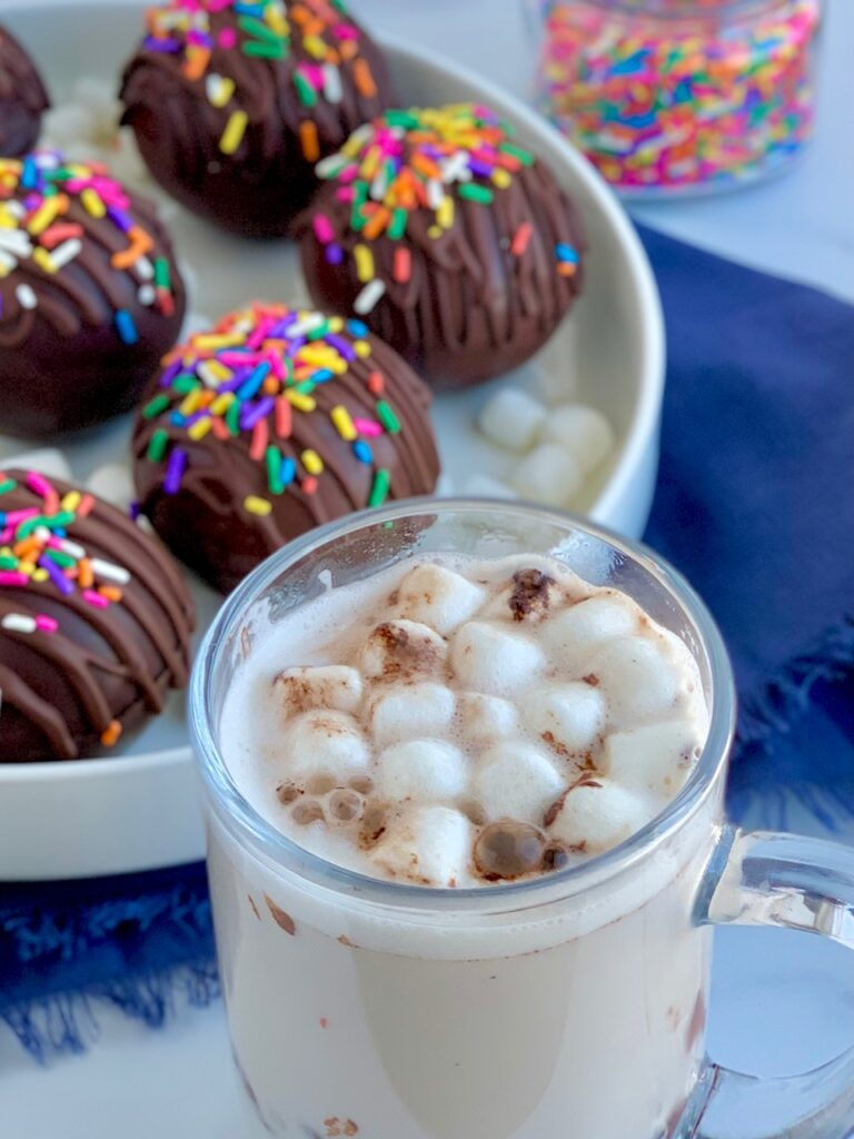A platter full of thin chocolate balls stuffed with hot chocolate mix and mini marshmallows. The top of the balls are decorated with melted chocolate zig zagging across the top and topped with  colorful sprinkles. A a mug full of hot chocolate and mini marshmallows.