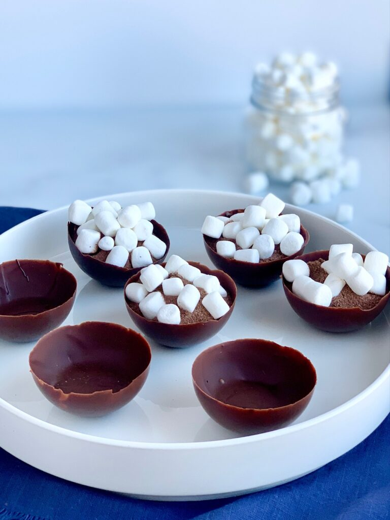 A platter full of 7 chocolate wells. Half of the chocolate wells are filled with hot chocolate mix and mini marshmallows. The other 3 are empty.