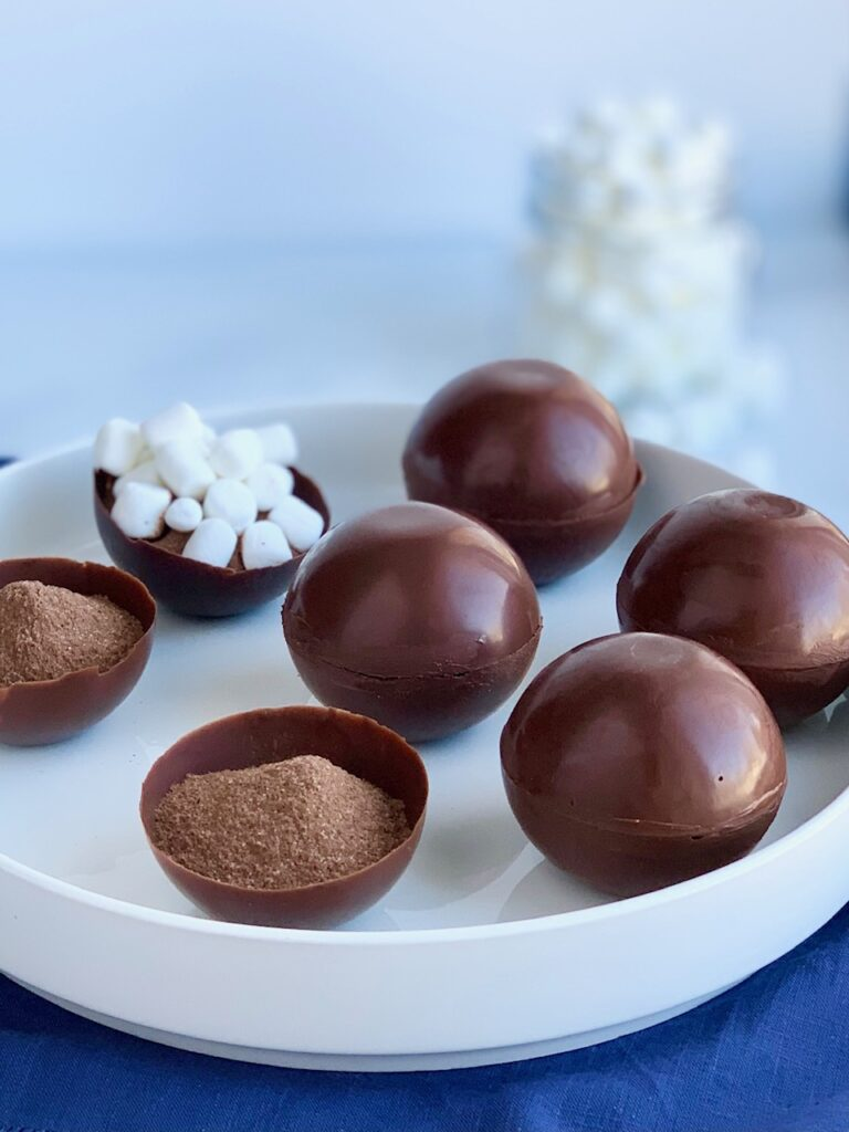 A platter full of thin chocolate balls stuffed with hot chocolate mix and mini marshmallows.
