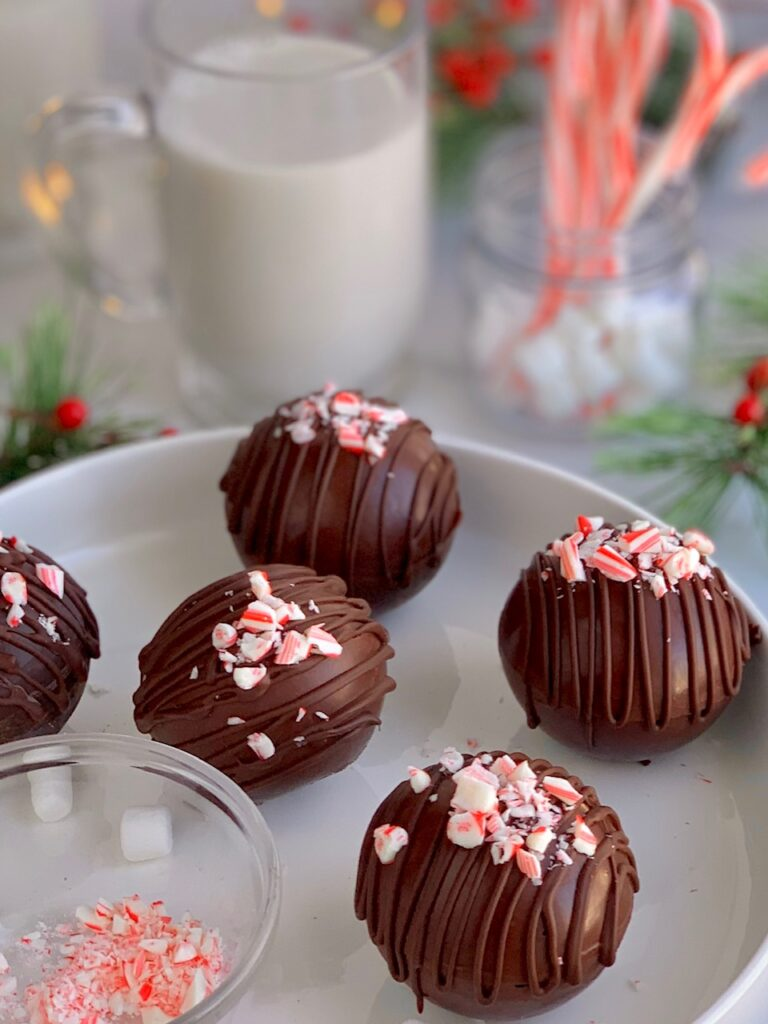 5 hollow chocolate balls filled with hot cocoa mix and topped with melted chocolate drizzle and crushed candy canes.