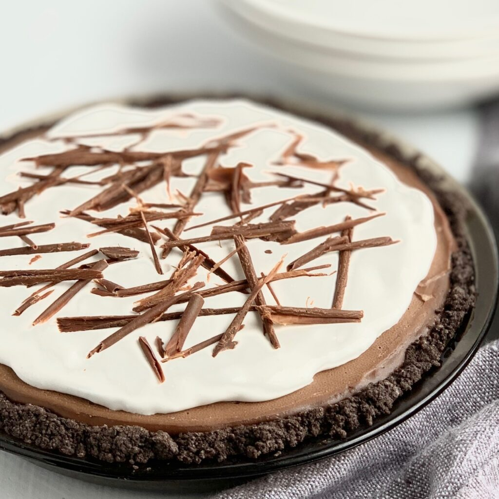 A pie plate filled with an oreo-like crust, creamy chocolate filling, a dairy free whipped topping and chocolate shavings.