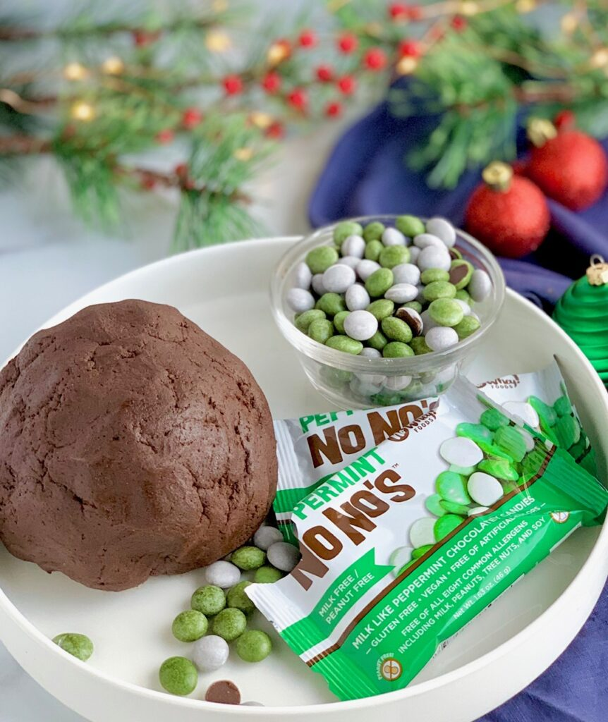 A large chocolate dough ball on a serving platter with a bowl of No Whey Food's Peppermint No No's (white and green peppermint candies)