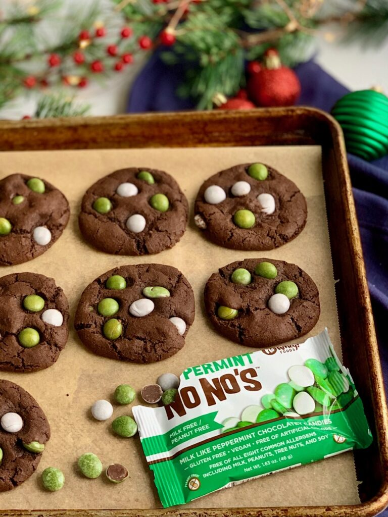 A baking sheet of baked chocolate cookies with green and white peppermint candies on top.