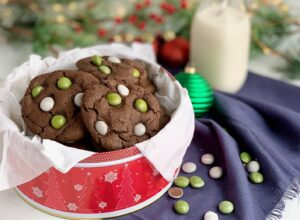 A festive red tin filled with chocolate cookies topped with peppermint candies.