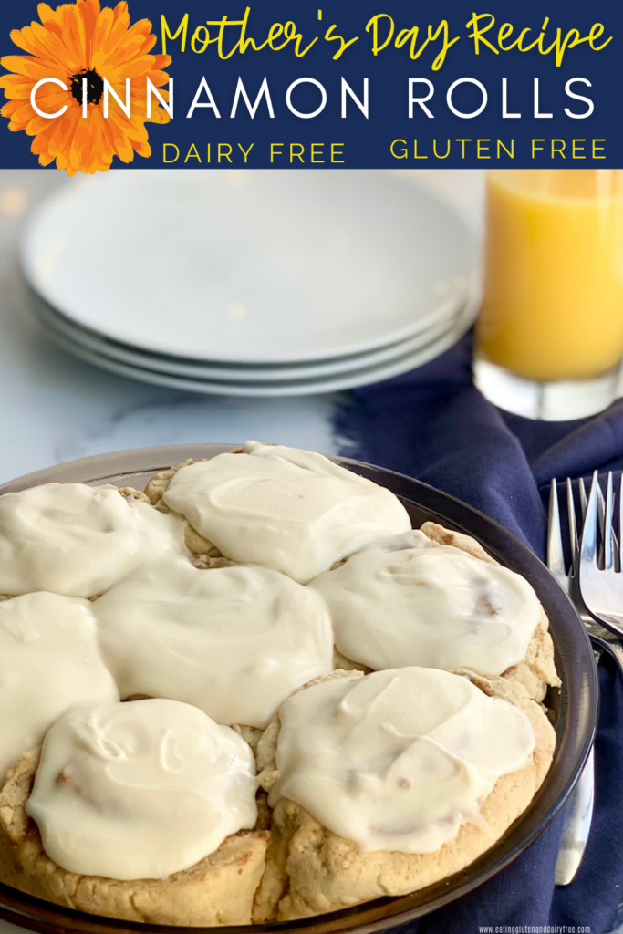 A pie plate filled with soft, gooey cinnamon rolls and topped with a decadent creamy dairy free cream cheese frosting next to serving plates and  glass of orange juice.