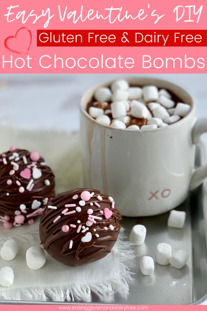 A hollow chocolate ball filled with hot chocolate mix and mini marshmallows. The outside of the ball has melted chocolate drizzle with white and pink sprinkles next to a mug of hot chocolate.