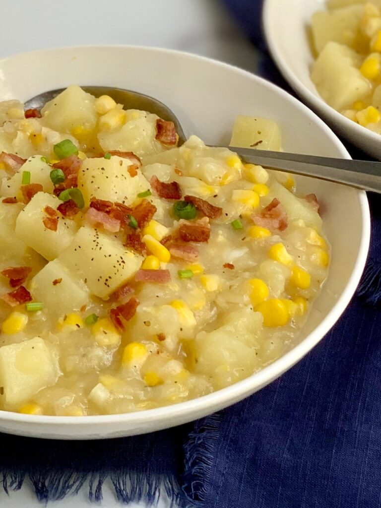 A soup bowl filled with potato corn chowder-- tender potato chunks, sweet corn topped with bacon pieces.