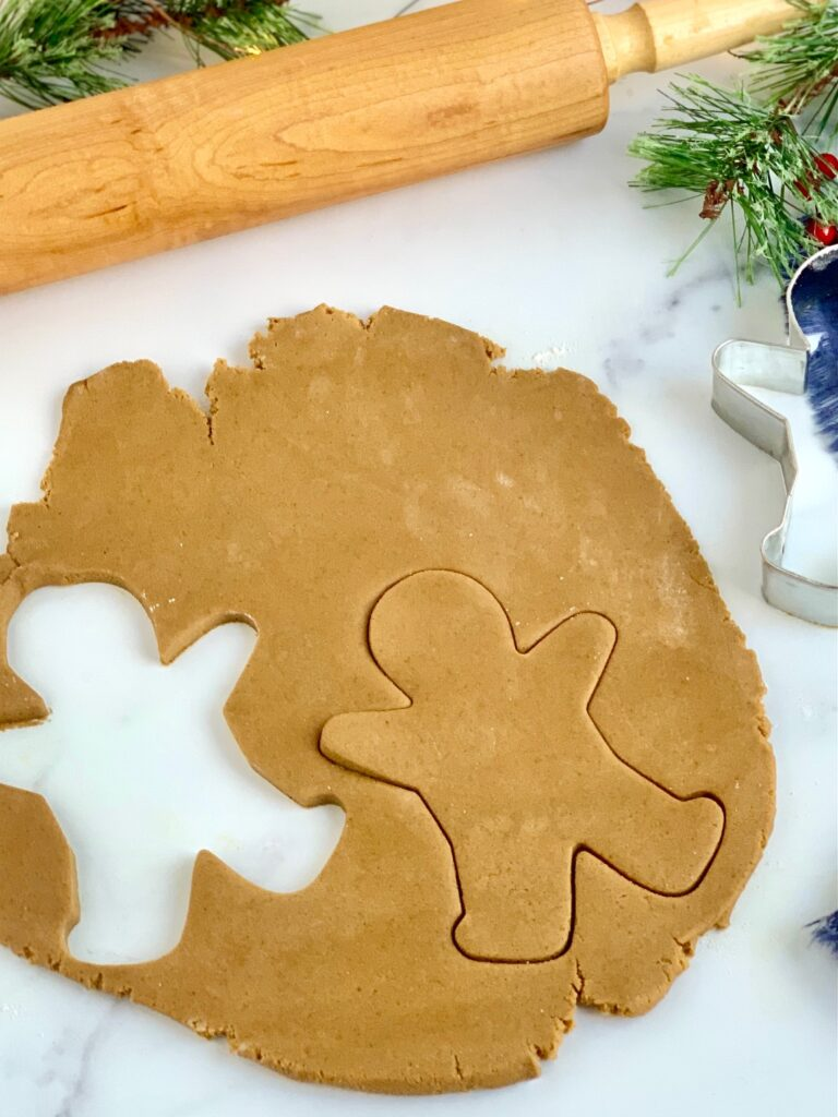 Gingerbread cookie dough rolled out  with a cookie cutter having cut out some cookies from the dough.