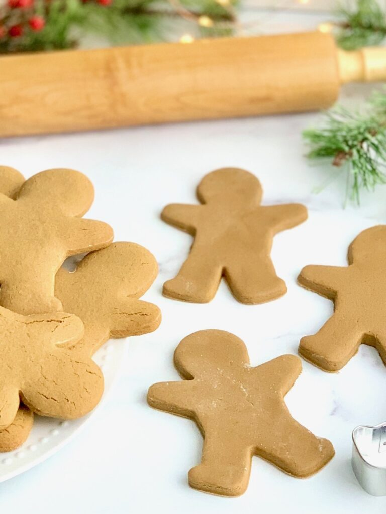 Gingerbread cookies on a countertop next to a rolling pin