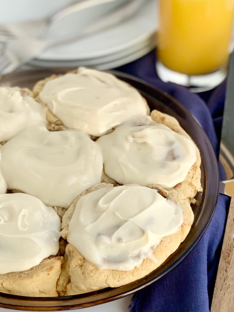 A pie plate full of 7 cinnamon rolls with a creamy cream cheese frosting.