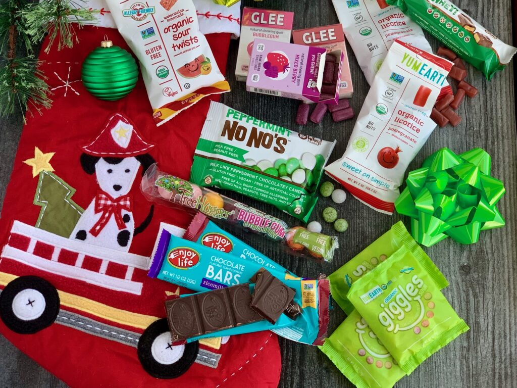 Several different allergen free snack ideas next to a red Christmas stocking.