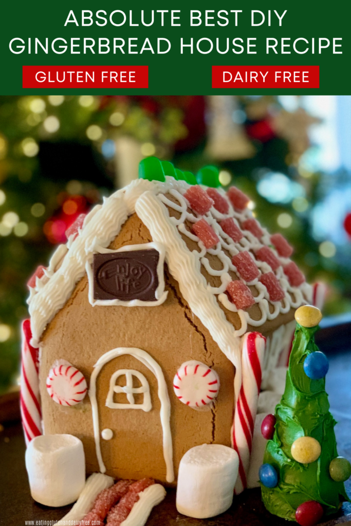 A gingerbread house decorated with frosting, candy, chocolate, marshmallows next to an upside down ice cream cone decorated as a tree with green frosting and colorful candies on it.