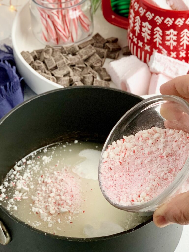 A mixture of granulated sugar, corn syrup, and crushed candy canes in a saucepan.