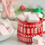 A red Christmas mug filled with hot chocolate and topped with fluffy pink peppermint marshmallows.